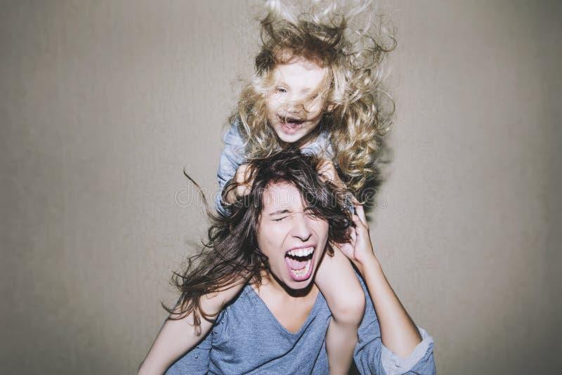 Kvinnan är skrikig och argumentera med ett barn på hans skuldror cli royaltyfri fotografi