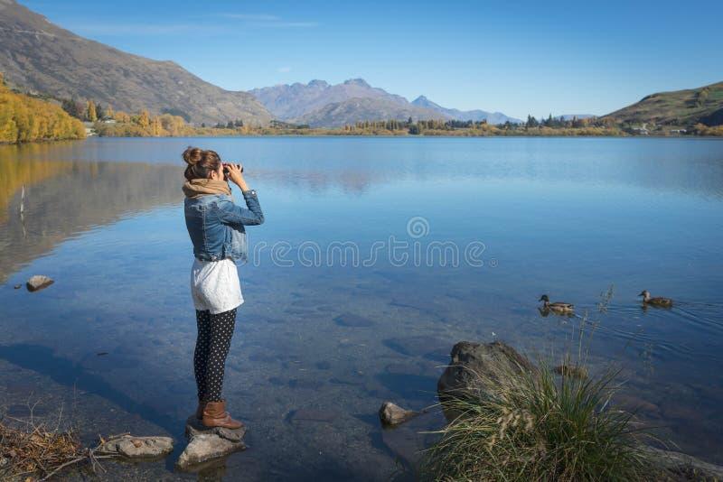 Kvinnan är stå och genom att använda kikare arkivfoton