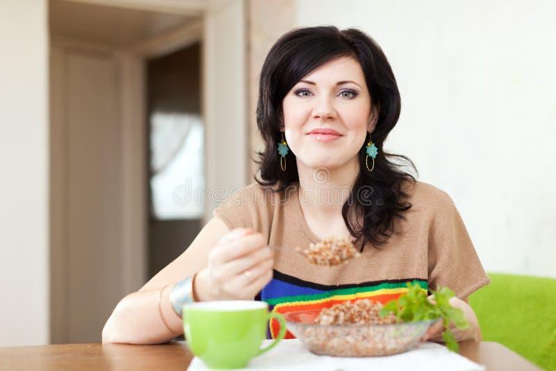 Kvinnan äter bovete royaltyfria bilder