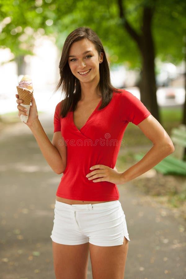 Kvinnan äter utomhus- söt glass parkerar in royaltyfri bild