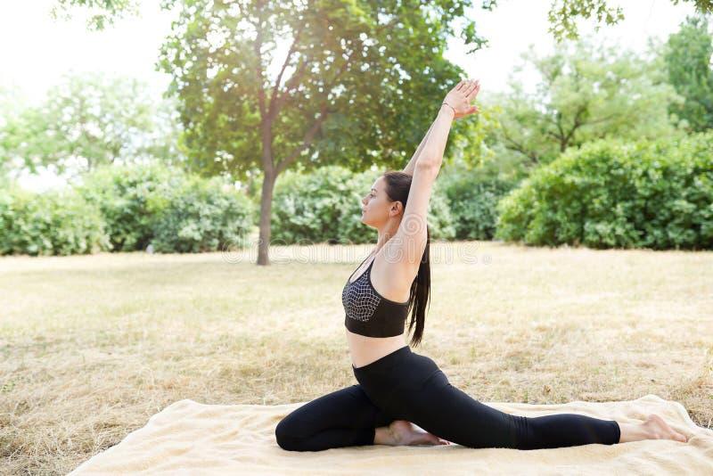 Kvinnan öva yoga och mediterar, naturbakgrund med kopieringsutrymme royaltyfria bilder