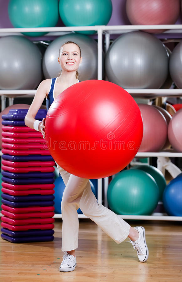Kvinnan övar med idrottshall klumpa ihop sig royaltyfri foto