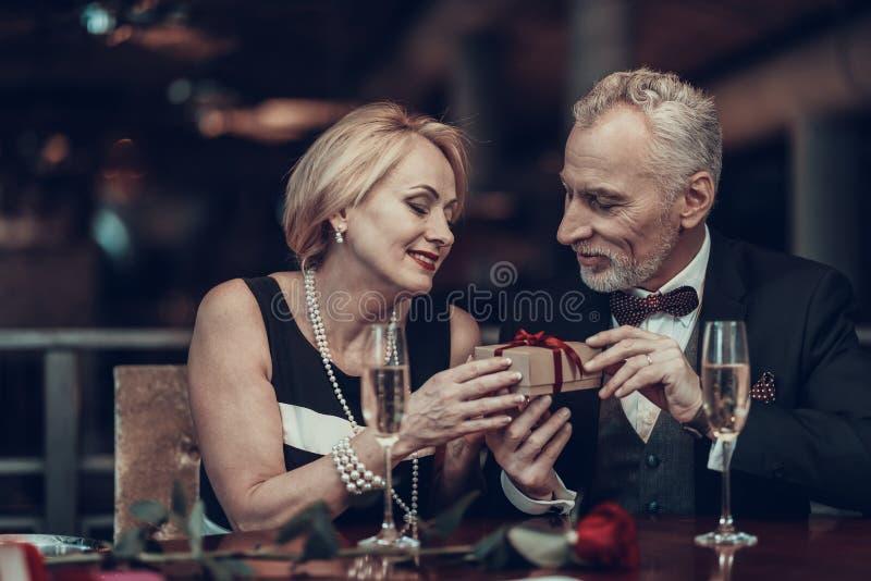 Kvinnan accepterar gåvan från affärsman i restaurang royaltyfria bilder