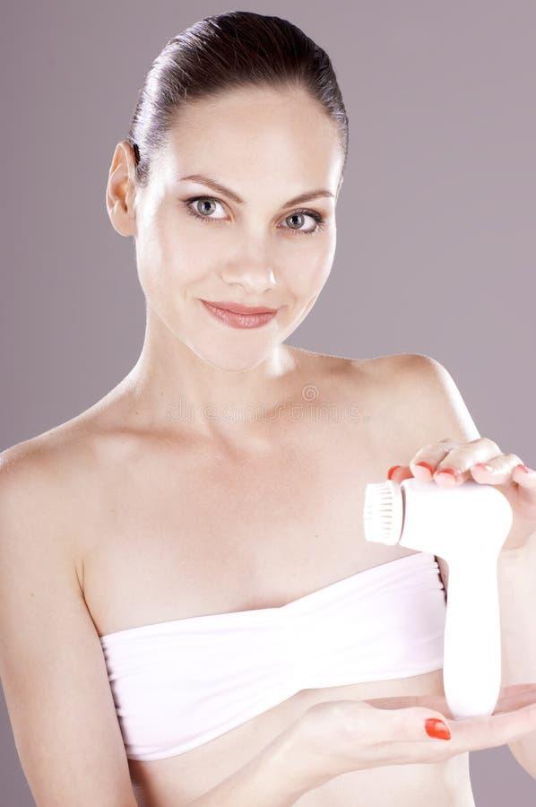 Kvinnan annonserar den elektriska borsten för djup rentvå ansiktsbehandling arkivbild