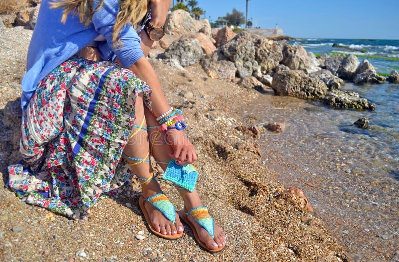 Kvinnan annonserar grekiska sandaler på stranden arkivbild
