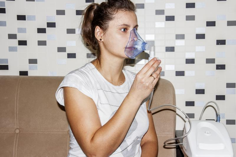Kvinnan använder en inhalator hemma, när hon hostar Behandling av respiratoriska sjukdomar Inandning med bronkit fotografering för bildbyråer