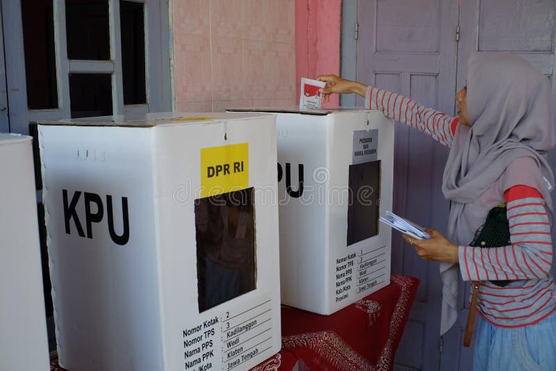 Kvinnan använder rösträtter i det indonesiska riksdagsvalet för president och vice presidentkandidater royaltyfria foton