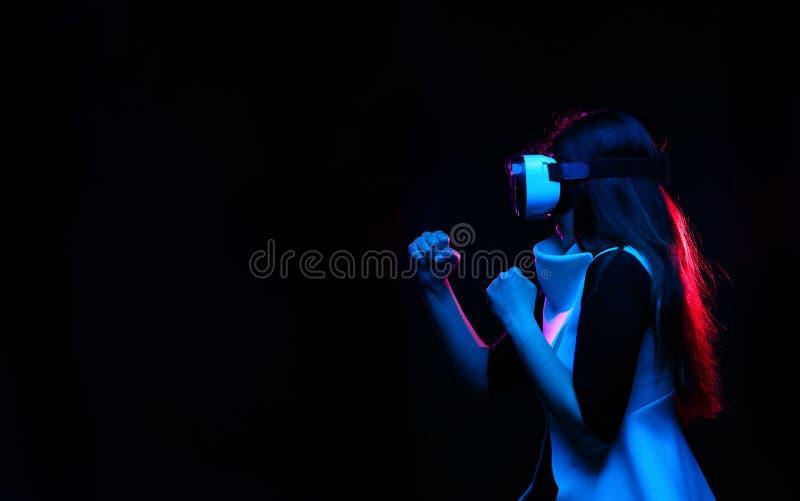 Kvinnan anv?nder virtuell verkligheth?rlurar med mikrofon Bild med tekniskt feleffekt royaltyfria foton