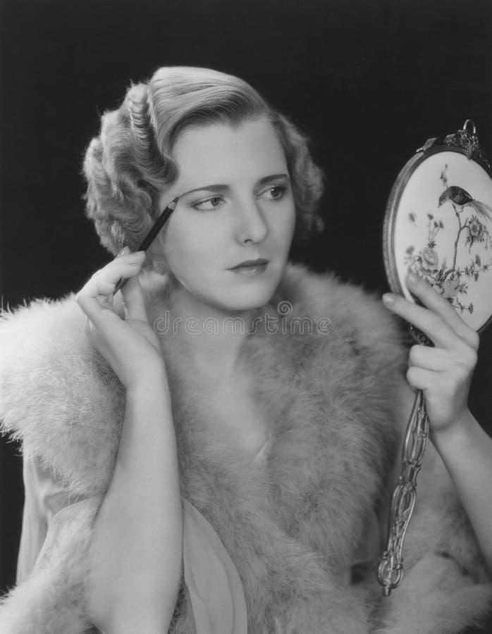 Kvinnan applicerar ögonbrynblyertspennan royaltyfri fotografi