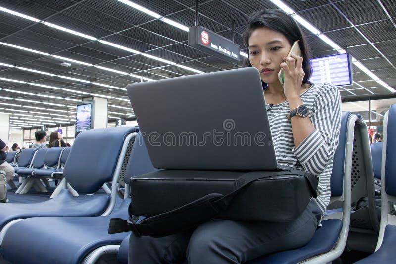 Kvinnan arbetar på en dator i en flygplats royaltyfri bild