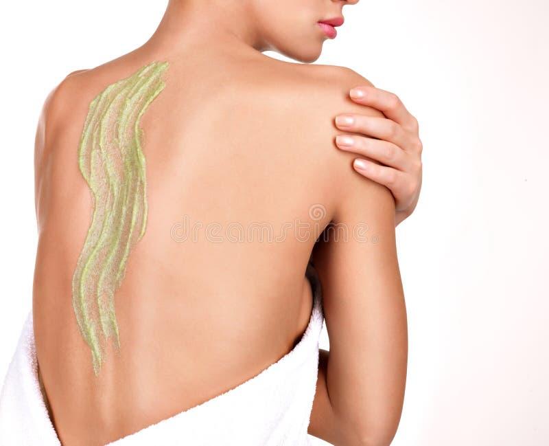 Kvinnan att bry sig om hud av kroppen som använder skönhetsmedlet, skurar på baksidan royaltyfria foton