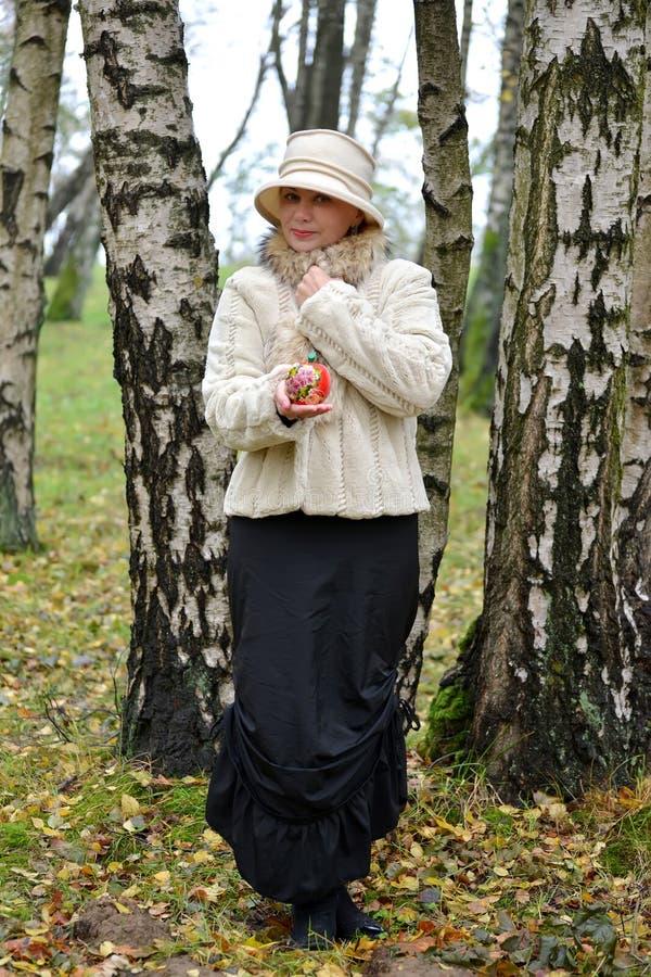 Kvinnan av genomsnittliga år i en hatt visar det dekorativa äpplet på en gömma i handflatan royaltyfria foton