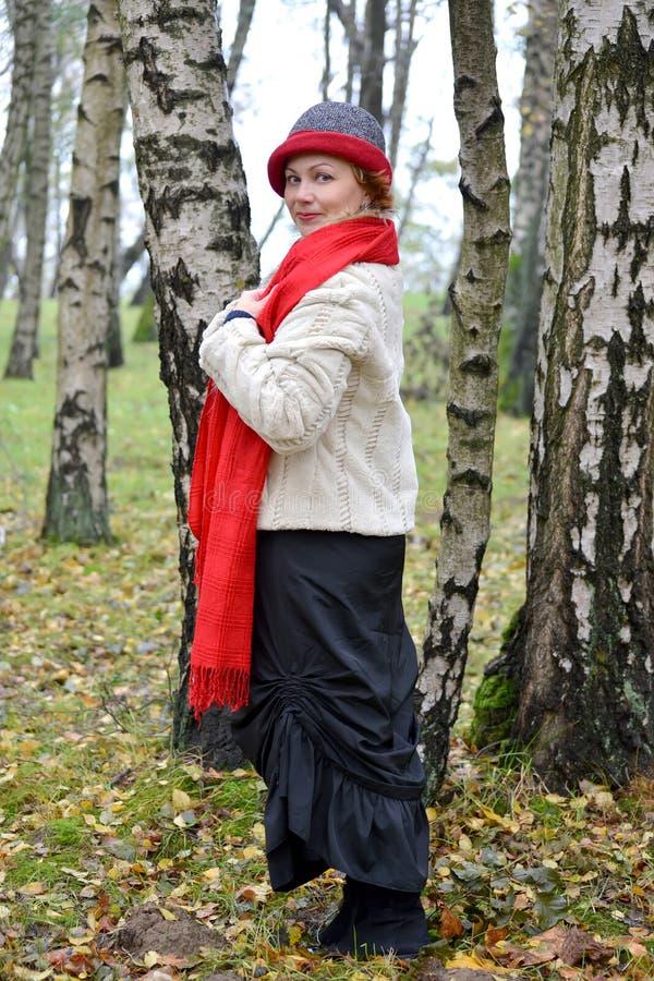 Kvinnan av genomsnittliga år i kostnader för en röd stola och för en hatt bland björkar i trät royaltyfria foton