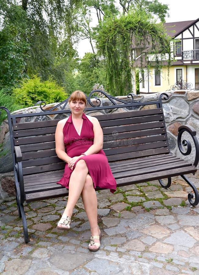 Kvinnan av genomsnittliga år sitter på en dekorativ bänk arkivfoto