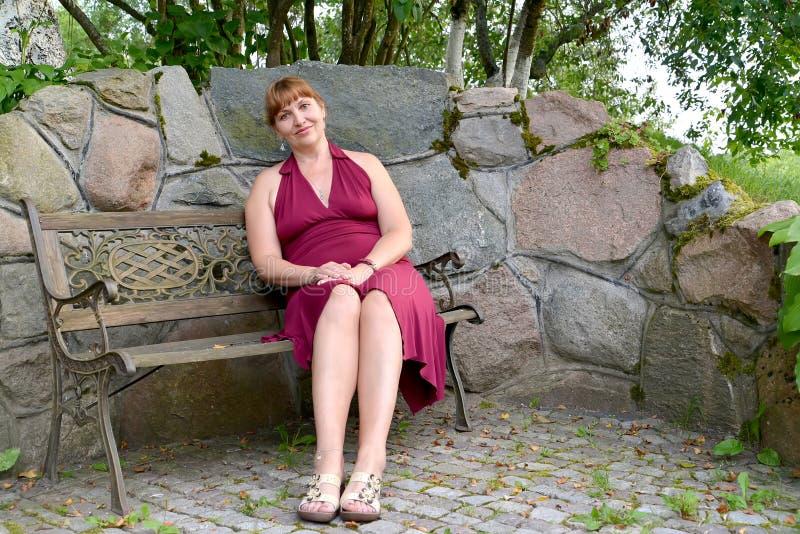 Kvinnan av genomsnittliga år sitter på en dekorativ bänk i parkera royaltyfri foto