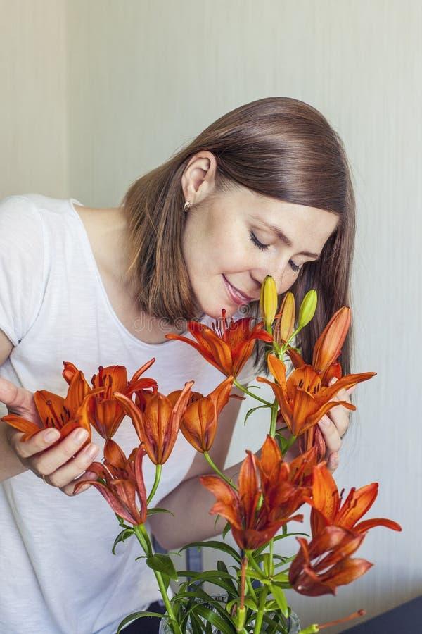 Kvinnan av huset inhalerar doften av orange stå för liljor fotografering för bildbyråer