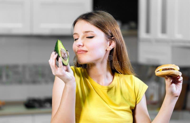 Kvinnan avgör mellan avokadot och hamburgaren royaltyfri foto