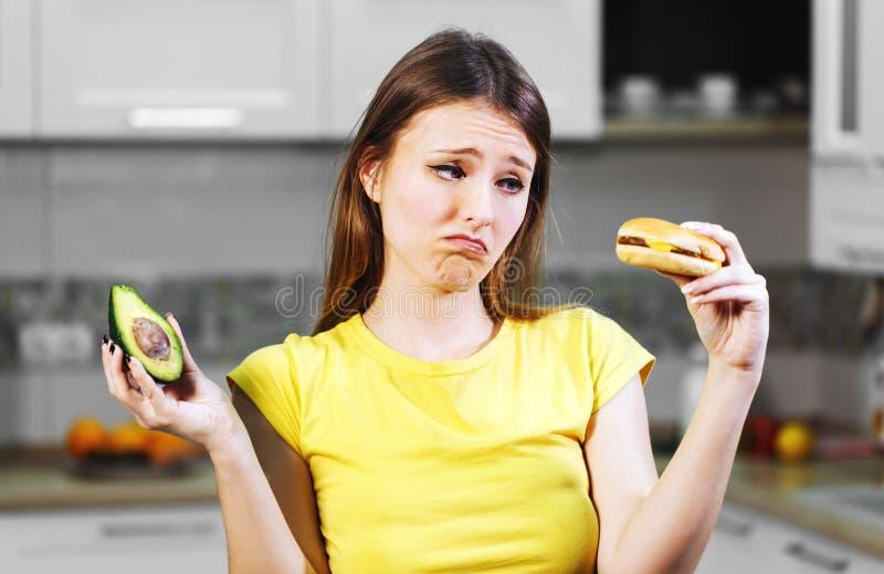 Kvinnan avgör mellan avokadot och hamburgaren fotografering för bildbyråer