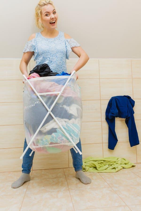 Kvinnan bär den stora korgen av den smutsiga klädertvätterit royaltyfri fotografi
