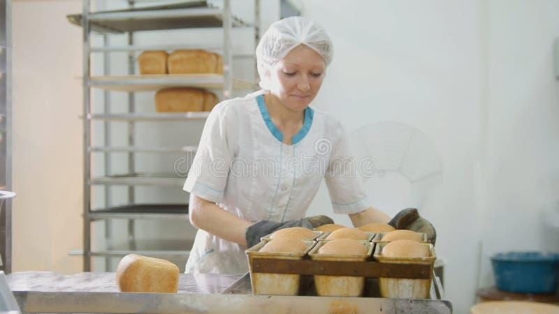 Kvinnan bakar bröd på kommersiellt kök arkivfoto