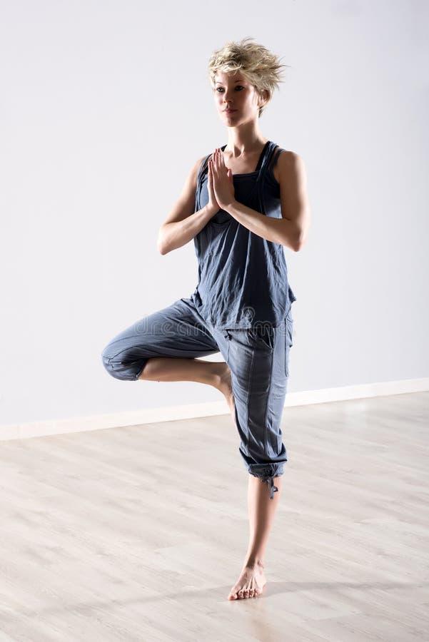 Kvinnan balanserade på ett ben i yogaposition arkivbilder