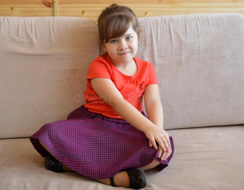 Kvinnan barnet, soffan som är ung, sammanträde, hem, behandla som ett barn, litet, lyckligt, soffan som är härlig, ungen, vit, ru fotografering för bildbyråer