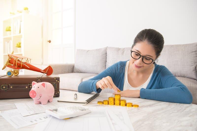 Kvinnan beräknar beloppet av guld- mynt arkivfoto