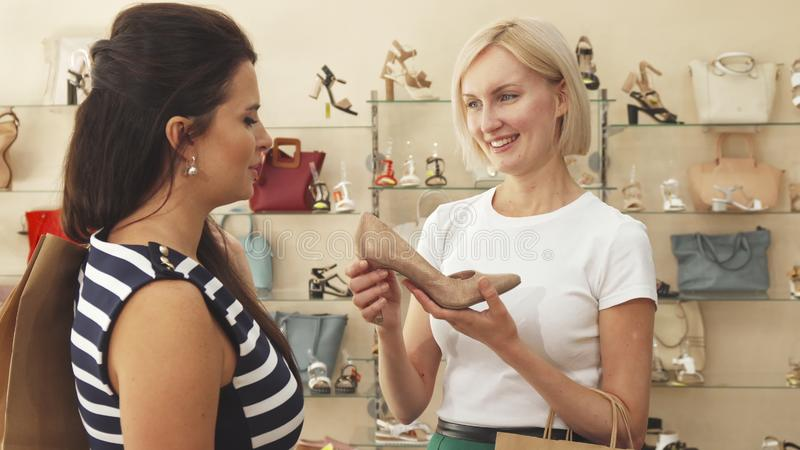 Kvinnan beundrar beigea skor med vännen arkivbild