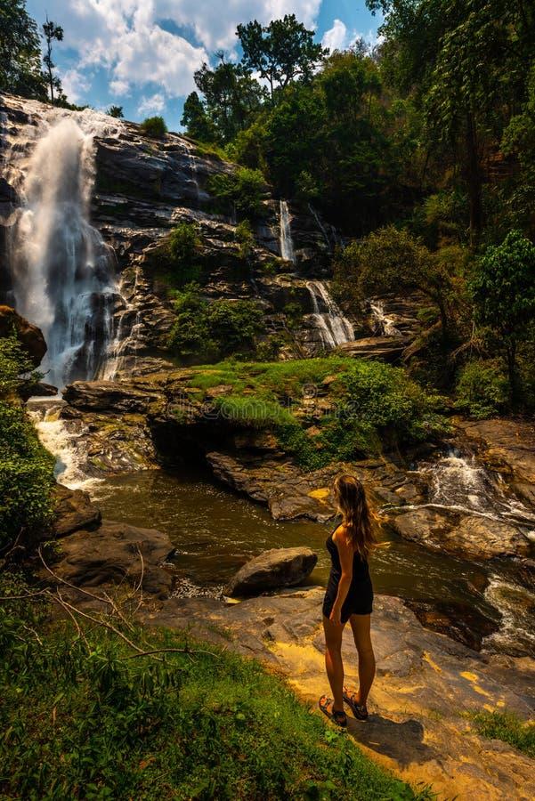 Kvinnan beundrar den Wachirathan vattenfallet i den Doi Inthanon nationalparken nära Chiang Mai Thailand royaltyfria foton