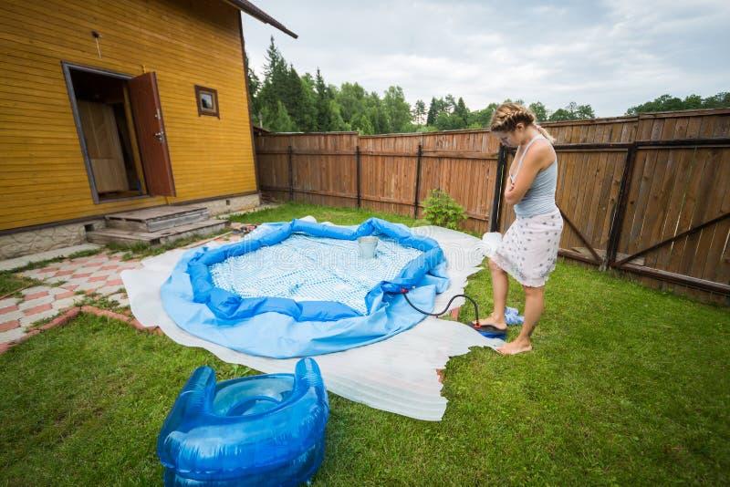 Kvinnan blåser upp den uppblåsbara simbassängen arkivbilder