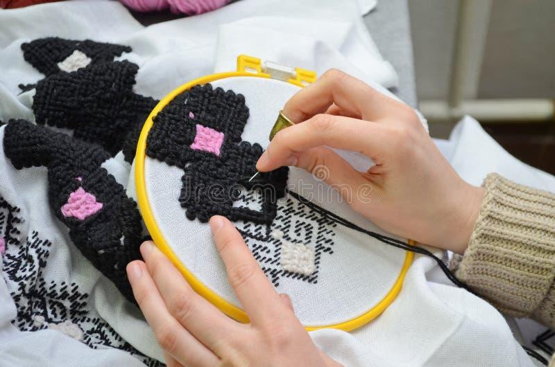Kvinnan broderar vid handbroderi på vitt tyg med svarta och rosa ulltrådar i beslaget, makro för bästa sikt arkivbild