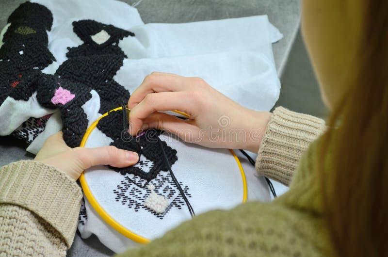 Kvinnan broderar vid handbroderi på vitt tyg med svarta och rosa ulltrådar i det gula beslaget, vänster siktsmakro royaltyfri foto
