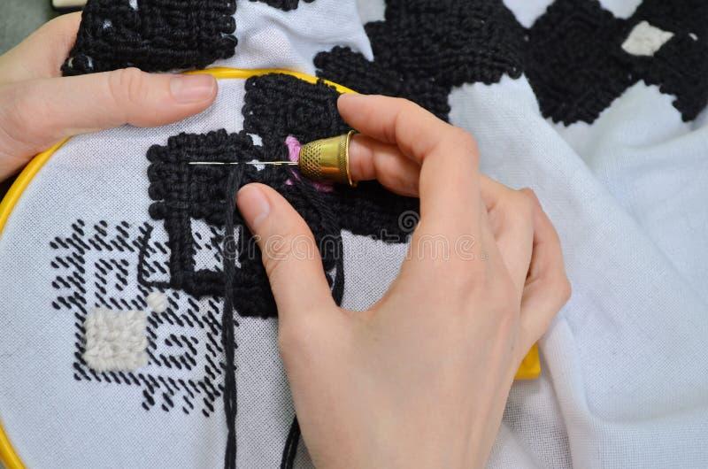Kvinnan broderar vid handbroderi på vitt tyg med svarta och rosa ulltrådar i gult beslag, med en visare fotografering för bildbyråer