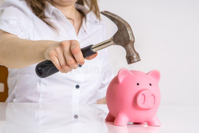 Kvinnan bryter den piggy pengarbanken med hammaren för att ta henne besparingar arkivfoto