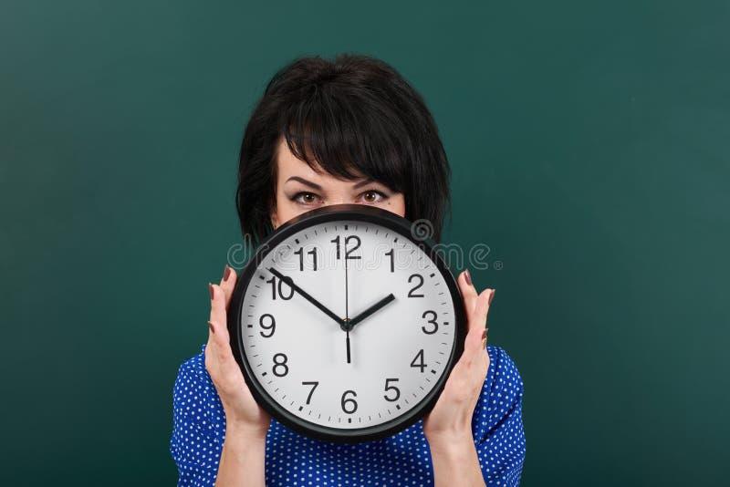 Kvinnan döljer hennes framsida bak klockan som poserar vid kritabrädet, tid och utbildningsbegreppet, grön bakgrund, studioskott arkivfoton