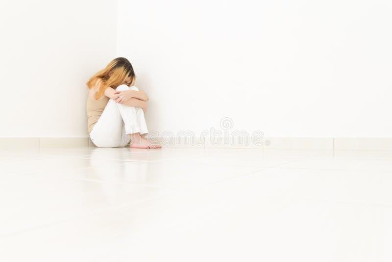 Kvinnan döljer hennes framsida mellan henne knä Väggarna är vita och arkivfoton