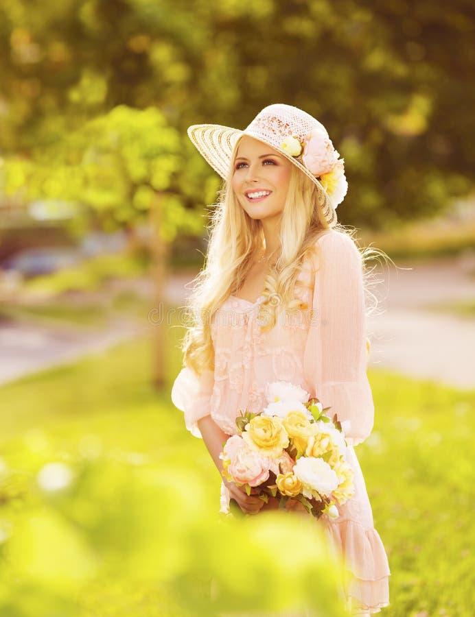 Kvinnan danar utomhus ståenden, ung dam i sommarhattklänning arkivfoto