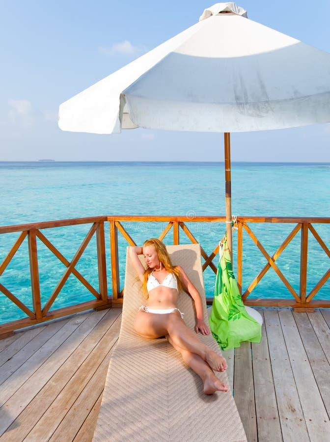 Kvinnan de solbada liesna för blondin på en chaisevardagsrum fotografering för bildbyråer