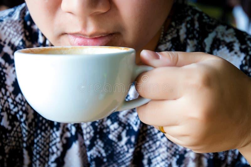 Kvinnan dricker kaffe på gatan dricker teakvinnan Kvinnan dricker utomhus- kaffe Affärskvinnan dricker utomhus- kaffe royaltyfri foto