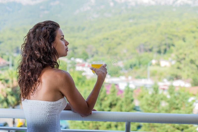 Kvinnan dricker orange fruktsaft på hotellbalkongen arkivbilder