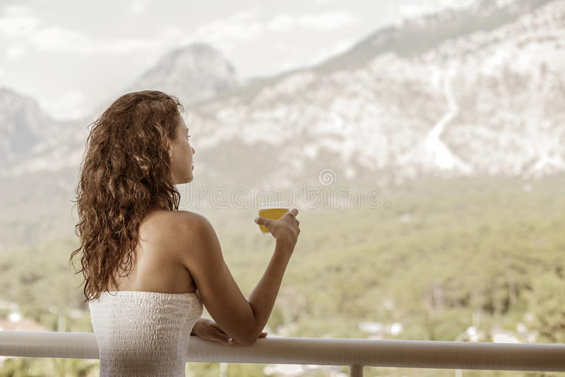 Kvinnan dricker orange fruktsaft på hotellbalkongen arkivfoton