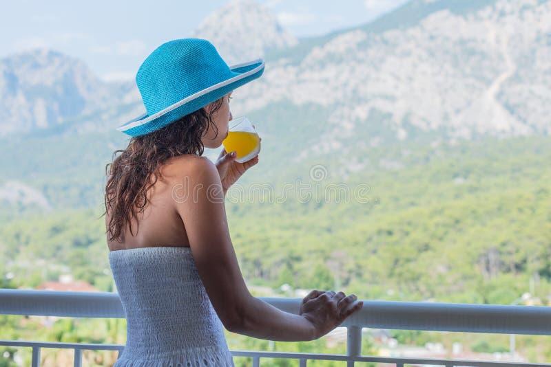 Kvinnan dricker orange fruktsaft på hotellbalkongen royaltyfri bild