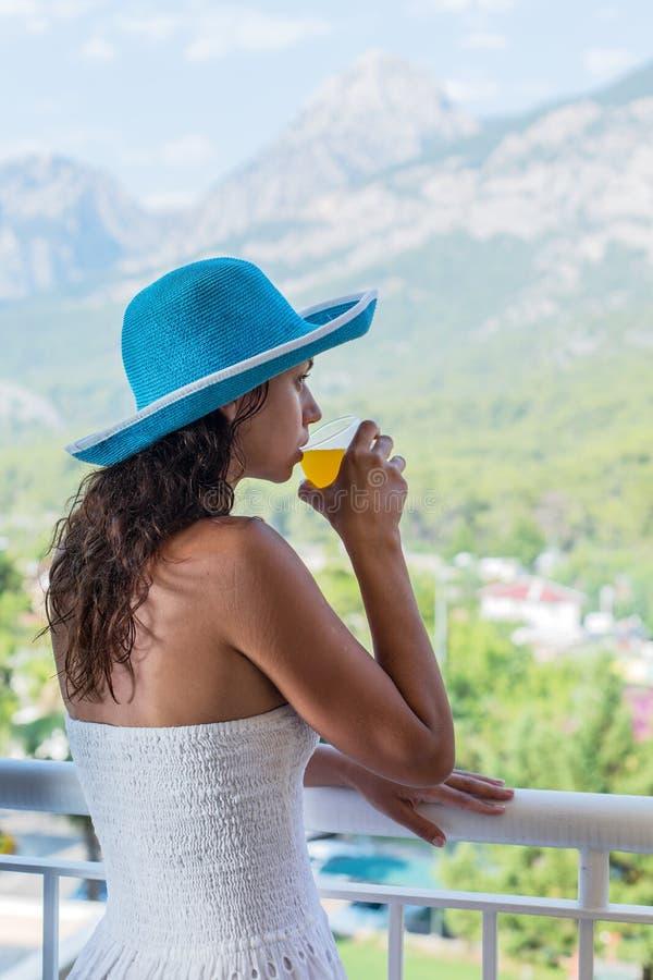 Kvinnan dricker orange fruktsaft på hotellbalkongen arkivfoto