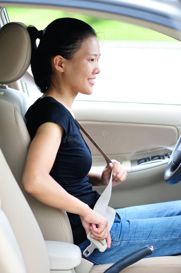 Kvinnan fäster bilbältet arkivfoto