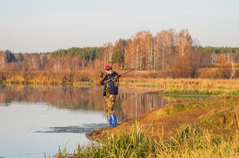 Kvinnan fångar en fisk på snurr royaltyfri bild