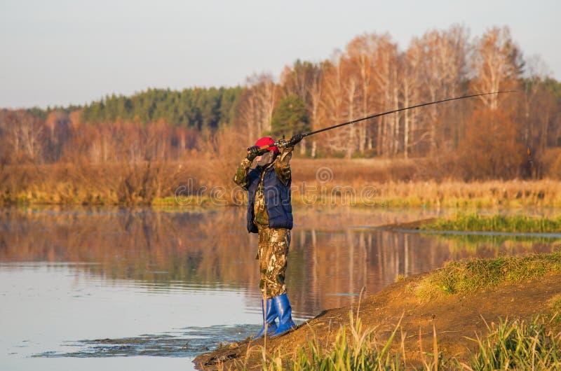 Kvinnan fångar en fisk på snurr fotografering för bildbyråer
