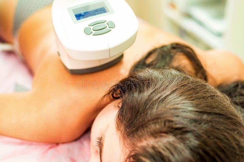 Kvinnan får anti--cellulite och anti--fett terapi i skönhetsalong fotografering för bildbyråer