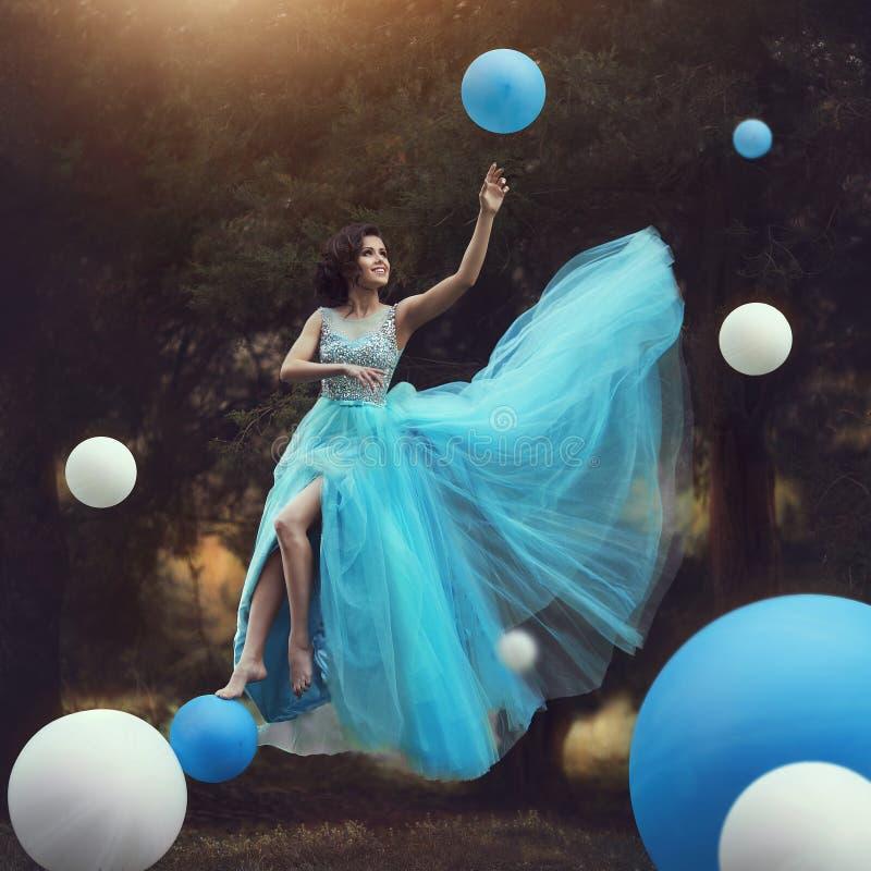 Kvinnan får att sväva En härlig flicka i en blå fluffig kappa Leets tillsammans med ballonger Dynamiskt konstfotografi fantasi arkivfoton