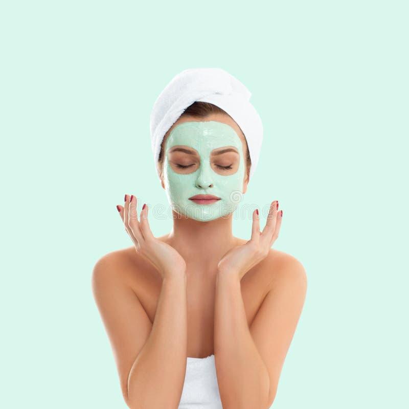 Kvinnan får den ansikts- leramaskeringen på pastellgräsplanbakgrund Skönhet och Spa royaltyfri foto