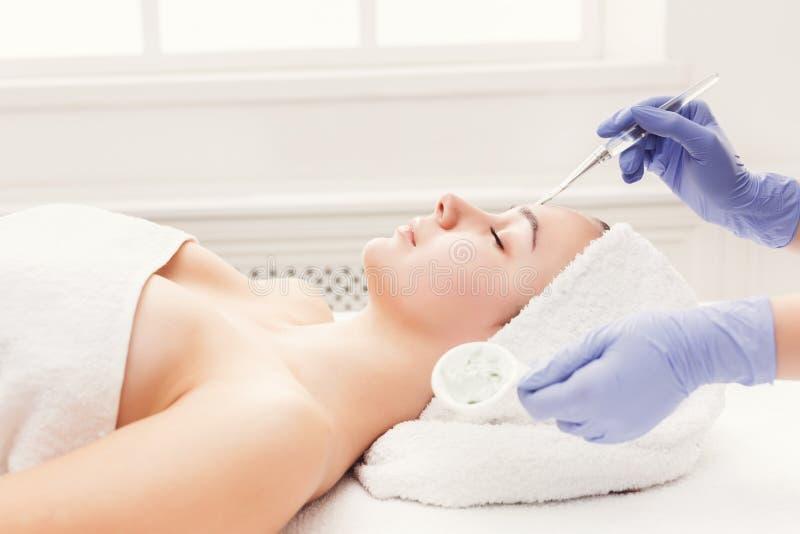 Kvinnan får framsidamaskeringen av kosmetologen på brunnsorten arkivfoton